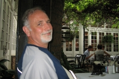 Rick Gifford smiles to the camera while seated at a table in a restaurant; a tree trunk is behind him, and greenery from the tree hangs down through the courtyard of the restaurant.