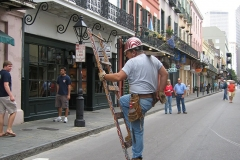 A man wearing a hard hat climbs a free standing ladder in the middle of the street, on his right shoulder he balances a piece of wood; various old buildings line the street behind him