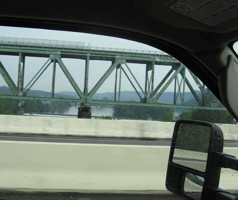 A trestle bridge spans over the Potomac river through the driver's side window; Rick Gifford is driving the truck