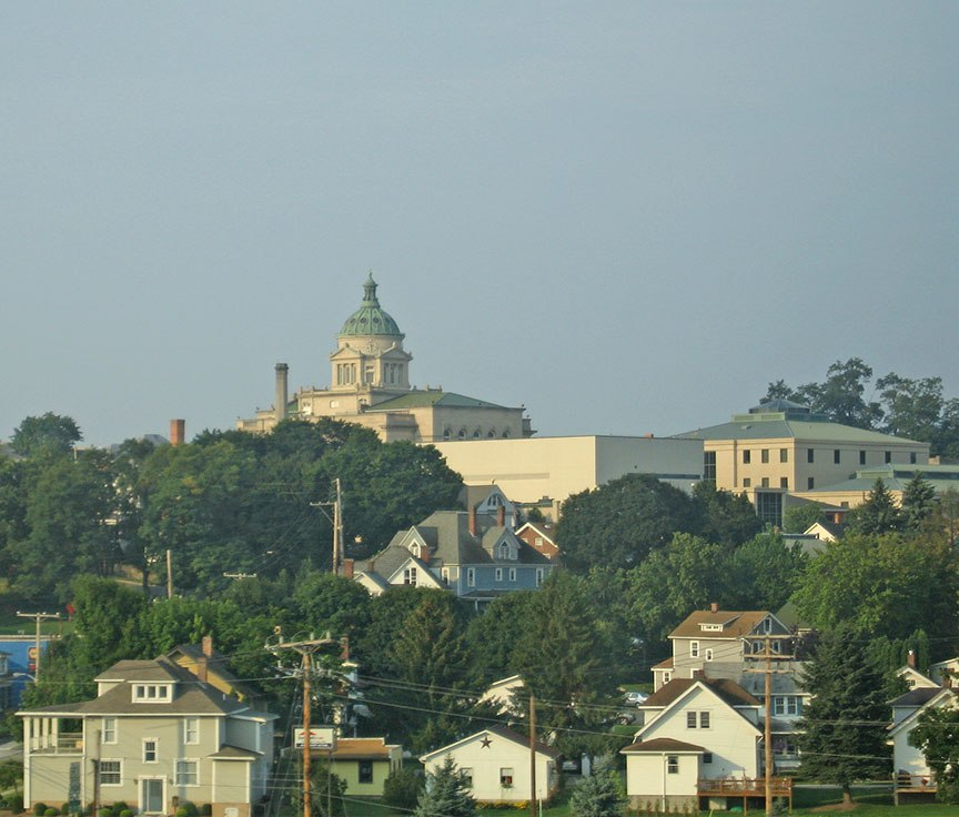 A white building with a green copper dome stands on a hill overlooking other buildings in town