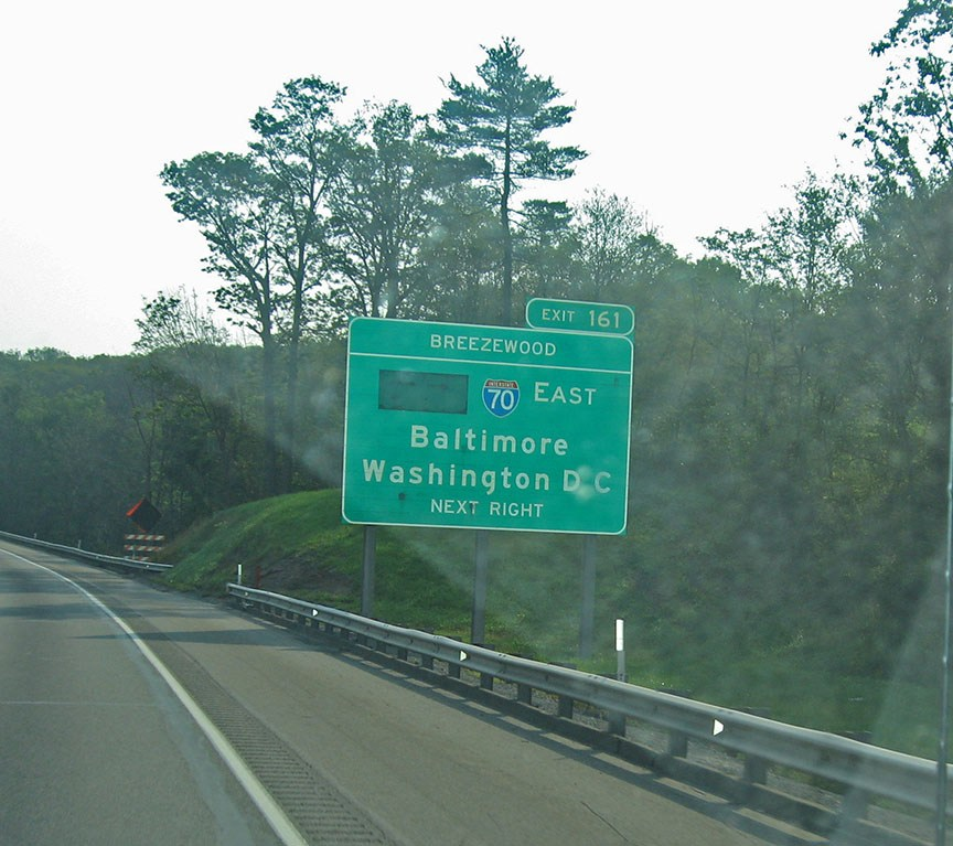 """A green freeway sign reads """"Baltimore, Washington D.C."""" and stands off the shoulder of the road"""