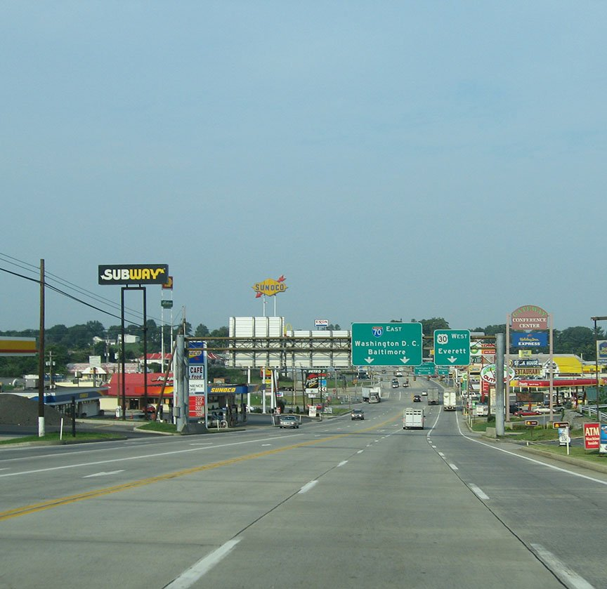 The highway is lined with various business including gas stations and fast food; stretched over the freeway are directional signs for I70 East to Washington D.C and Baltimore