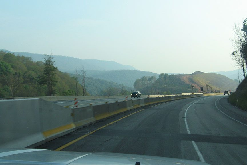 The road winds through low level hills that are covered with trees; blue skies with white clouds stretch out overhead