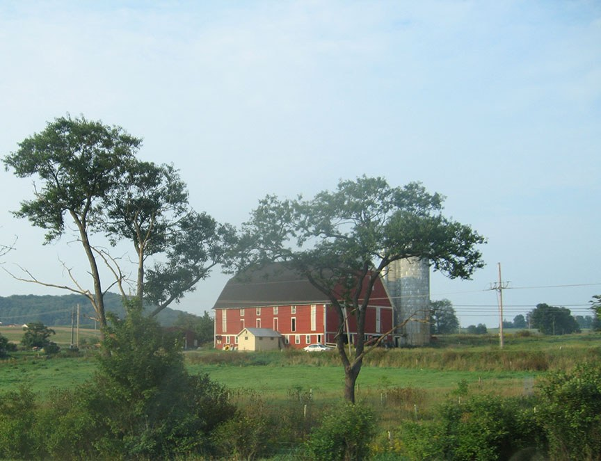 A traditional red barn with silo stands in the middle of a field behind some trees, blue skies stretch out overhead
