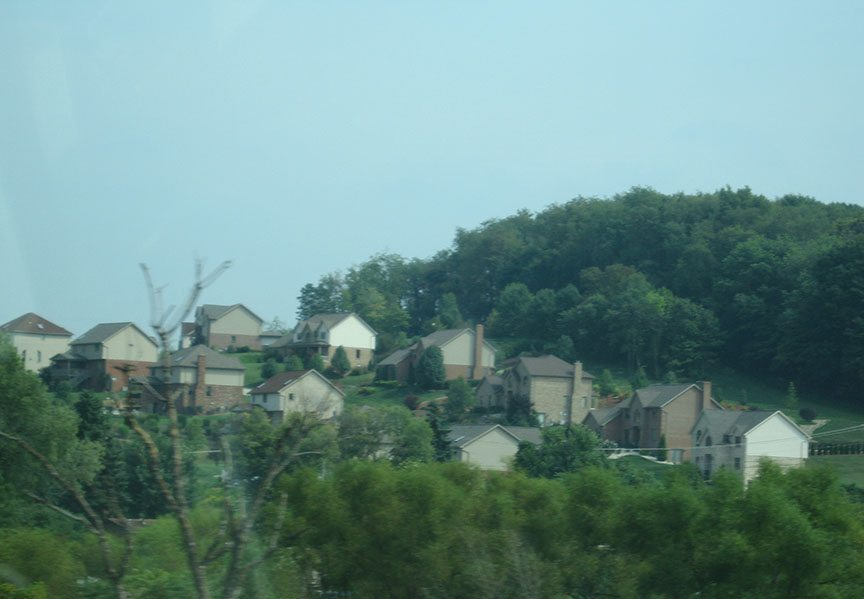 A neighborhood of upscale houses, mostly brick, stands on a small hill between two groups of trees, blue sky above