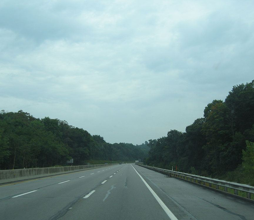 Three lanes of highway stretch out in front of the truck, trees line both sides of the highway
