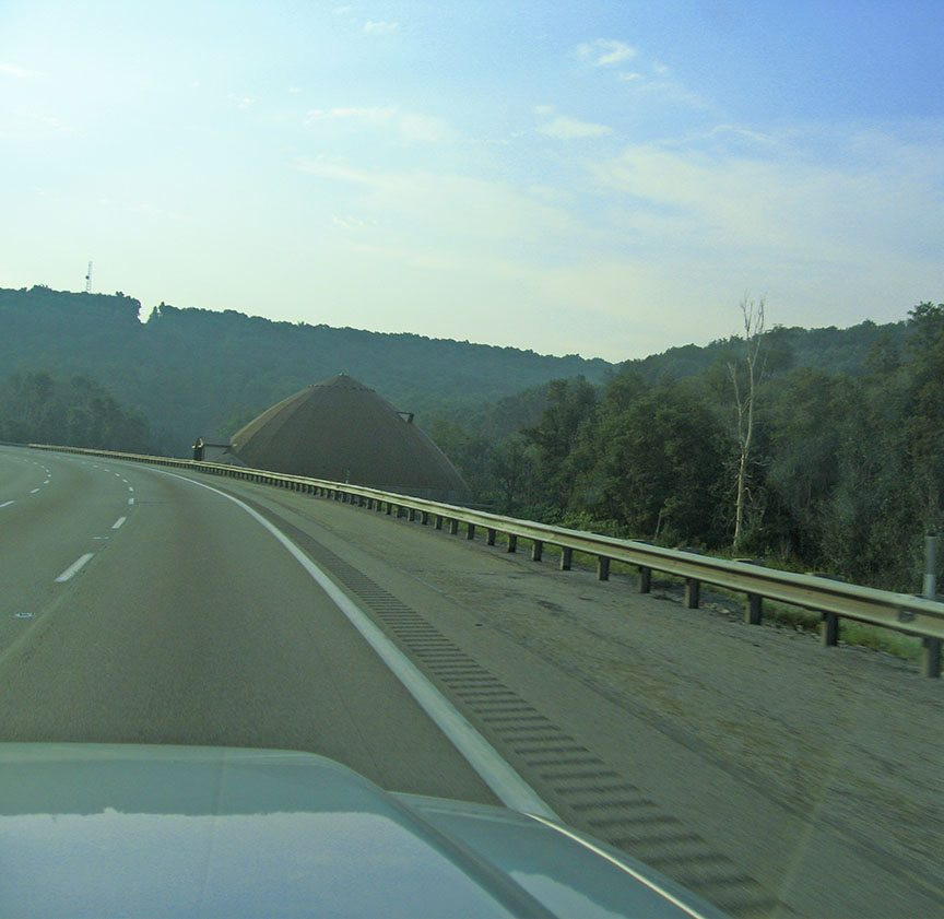 The pointed roof of a building peeks out over the shoulder of the highway; trees cover the rolling hills behind it