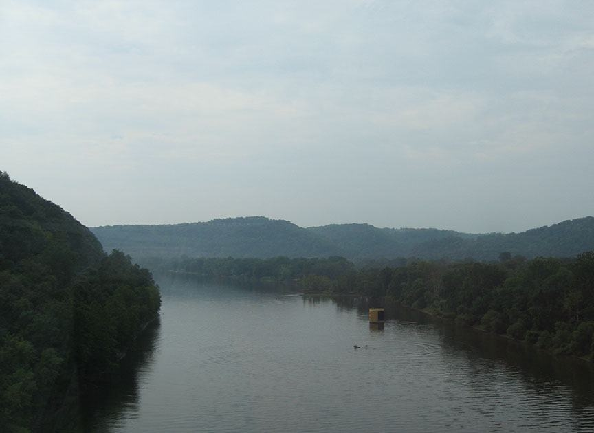 The Potomac River stretches out with tree lined banks, a cloud filled sky overhead