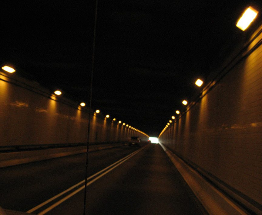 Lights illuminate a darkened tunnel - at the far end, the light from outside glows