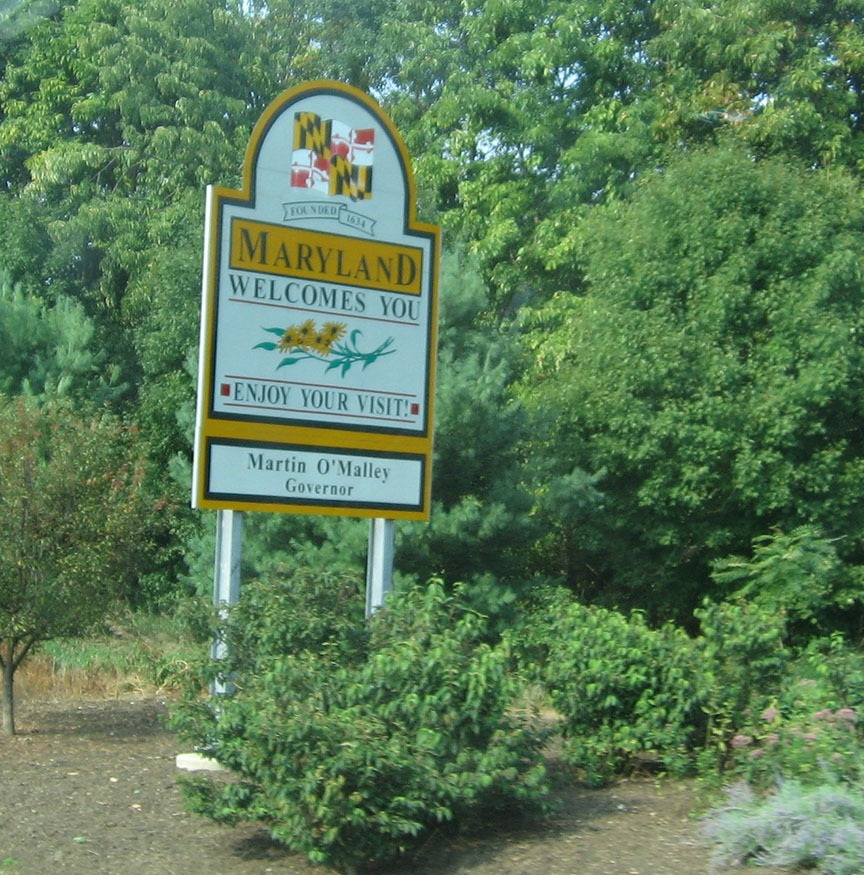 "A white and yellow sign stands on the should off the road and reads ""Maryland Welcomes You"""