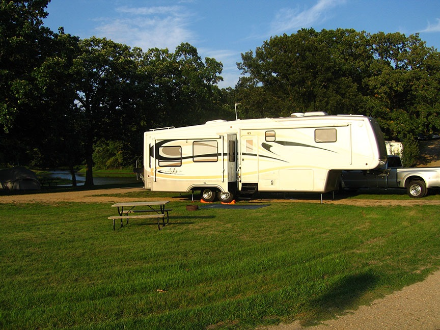 The fifth wheel is backed into a spot along the water, nestled among the trees; green grass stretches out next to it with a picnic table