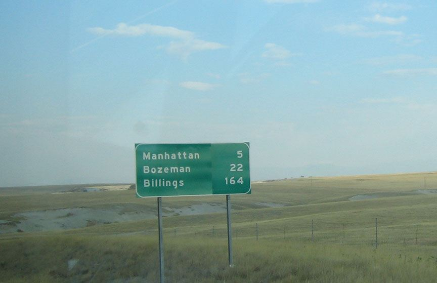 A distance to cities sign stands on the shoulder of the freeway it reads: Manhattan  5, Bozeman 22, Billings 164; bright blue sky stretches out behind it