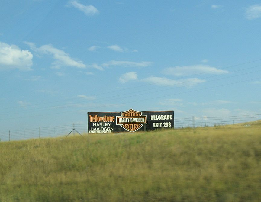 A sign for the Yellowstone Harley Davidson shop sits in a field off of the freeway backed by bright blue sky