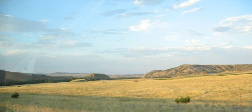 Dry grass spans out from the shoulder of the road with low, rocky foothills in the distance.