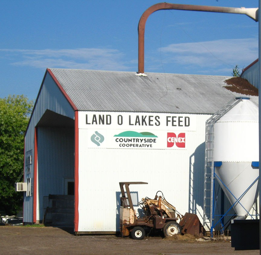 "A white building reading ""Land O Lakes Feed Countryside Cooperative"" stands behind the fifth wheel against blue sky"
