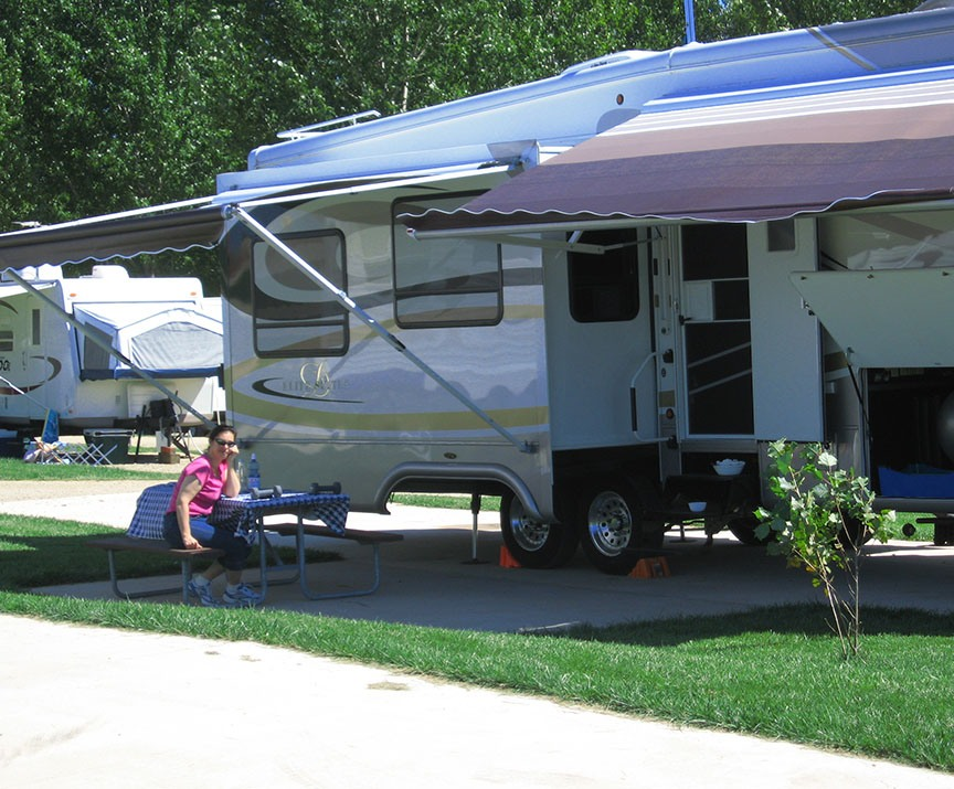The fifth wheel is extended, awnings open and Lisa Gifford sits at the picnic table under an awning, smiling to the camera