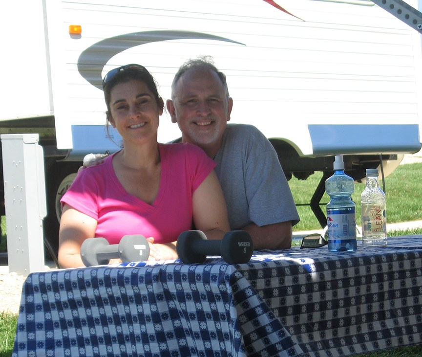 Lisa and Rick Gifford sit at a picnic table covered with a blue and white tablecloth, both are smiling to the camera