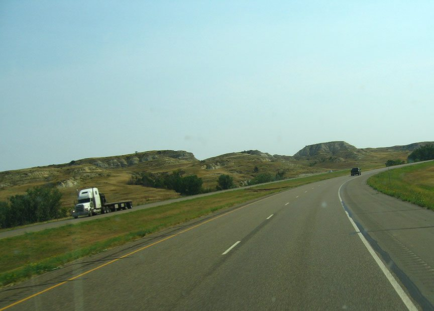 The road stretches in front of the truck; across the divided freeway, low foothills covered with dry grass roll against a blue sky