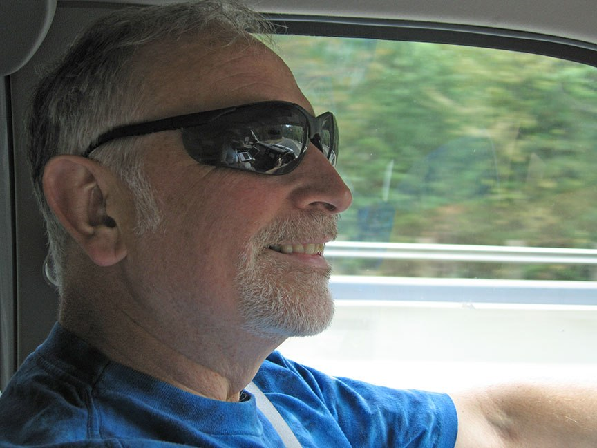 Rick Gifford, profile, smiles while driving the truck; greenery is a blur outside his window