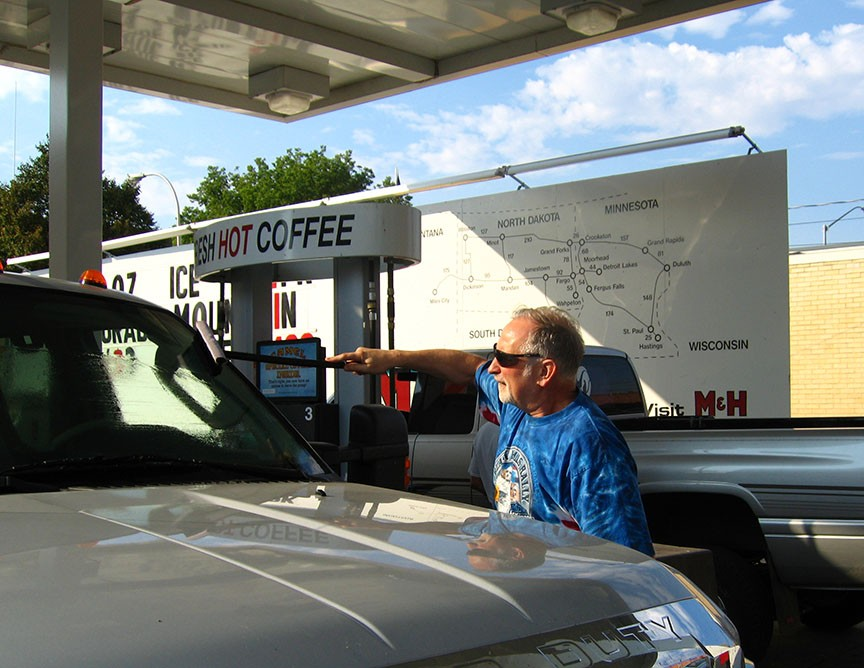 Rick Gifford cleans the driver's side windshield of the truck with a squeegee while stopped at a gas station