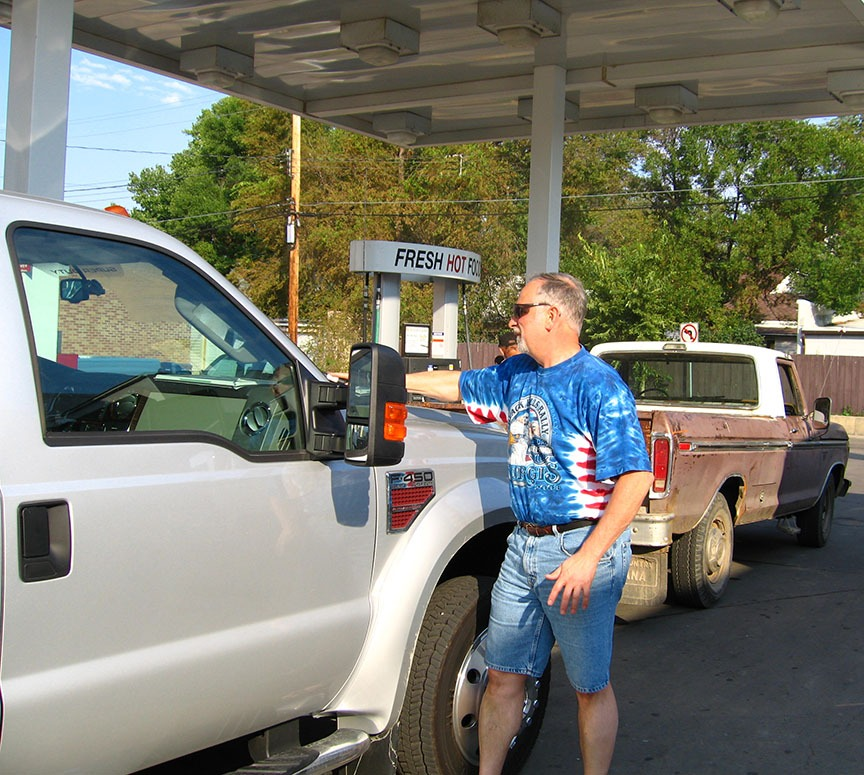 Rick Gifford cleans the passenger's side windshield of the truck with a squeegee while stopped at a gas station; a rusty red truck is parked at the pump in front of them
