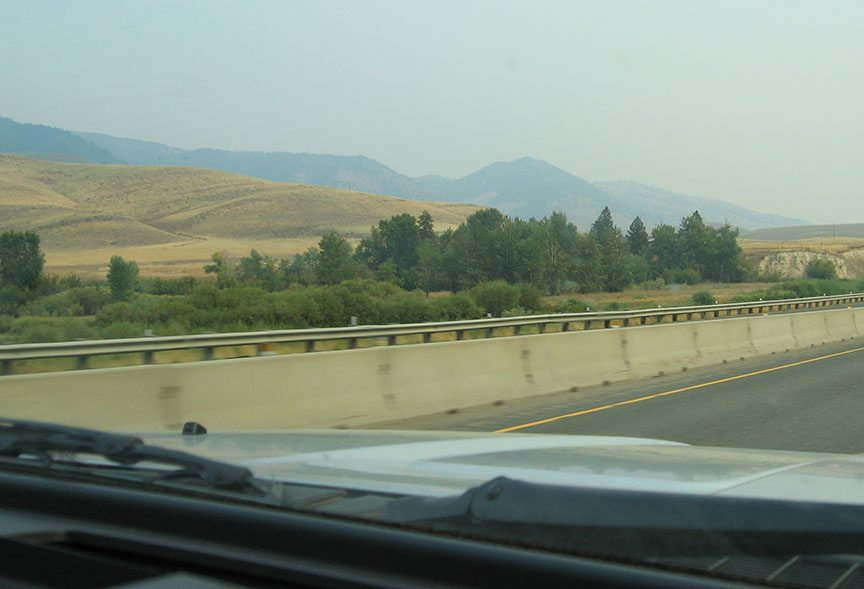 Road stretches out in front of the truck, low foothills in the distance covered by haze