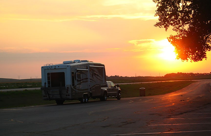 The truck and fifth wheel are parked at a rest stop while the sun rises in a riot of golds, pinks, and tangerines