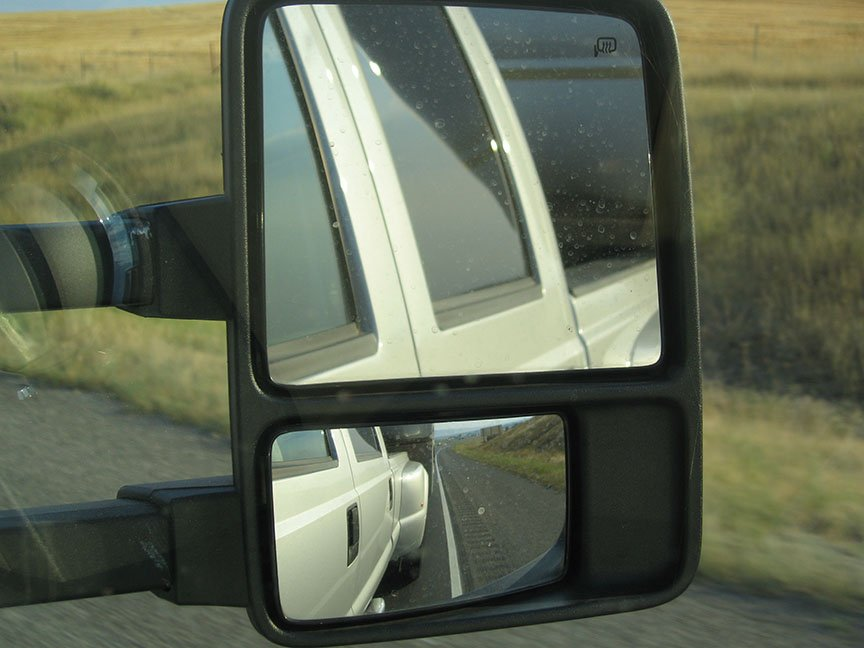 Side mirror of the truck with the truck side reflected in the mirror; grass rolls out from the shoulder of the road