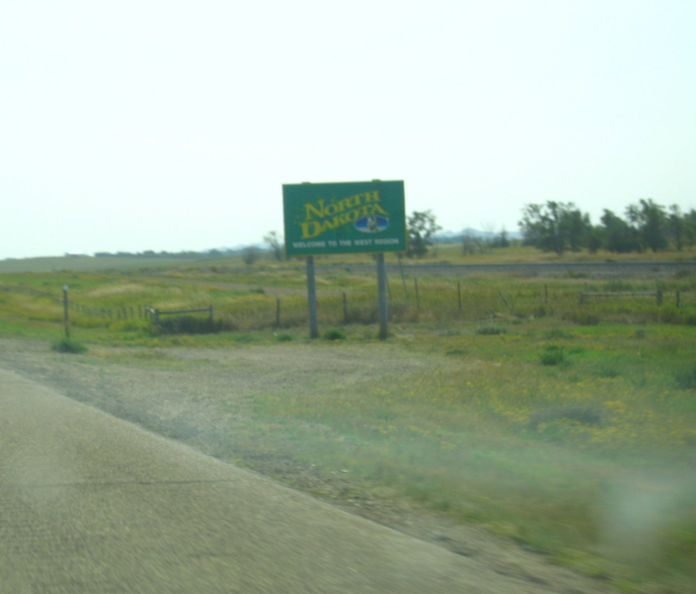 "A green sign with yellow letters stands on the shoulder of the road and reads ""North Dakota Welcome to the West Region"""
