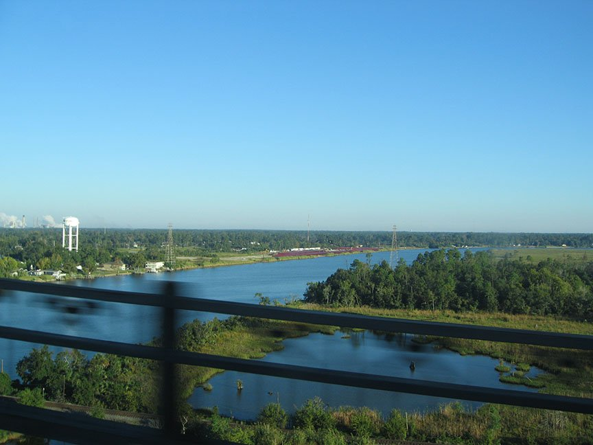 From out of the passenger window, a waterway flows away from an overpass; blue skies stretch out overhead