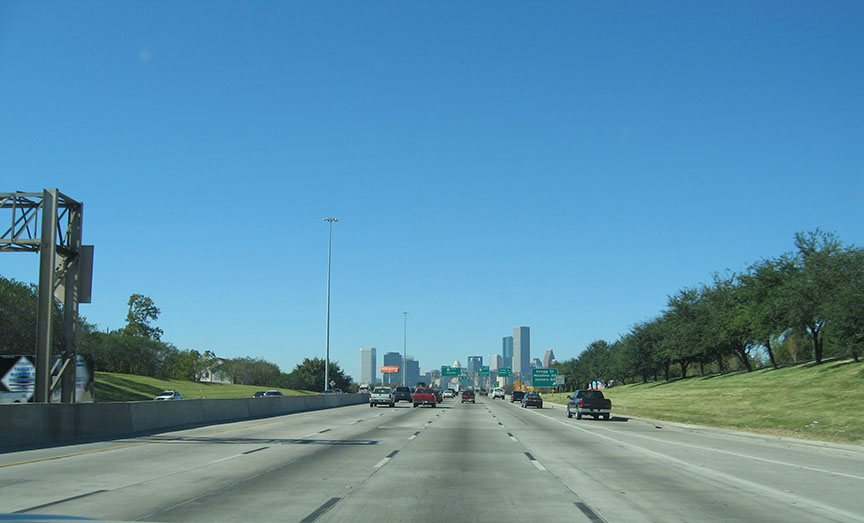 Five lanes of highway stretch in front of the truck leading to the downtown skyline of Houston against a bright blue sky