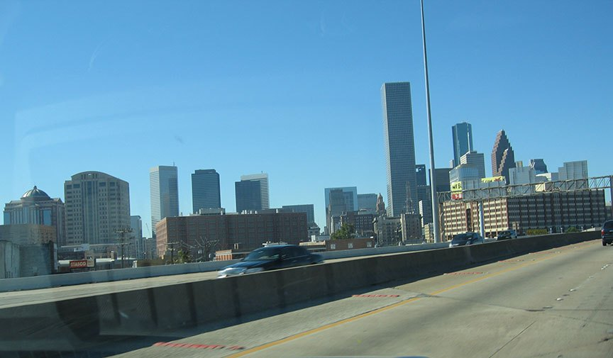 From the front windshield, over the highway, downtown Houston's skyline is displayed close up and against a bright blue sky