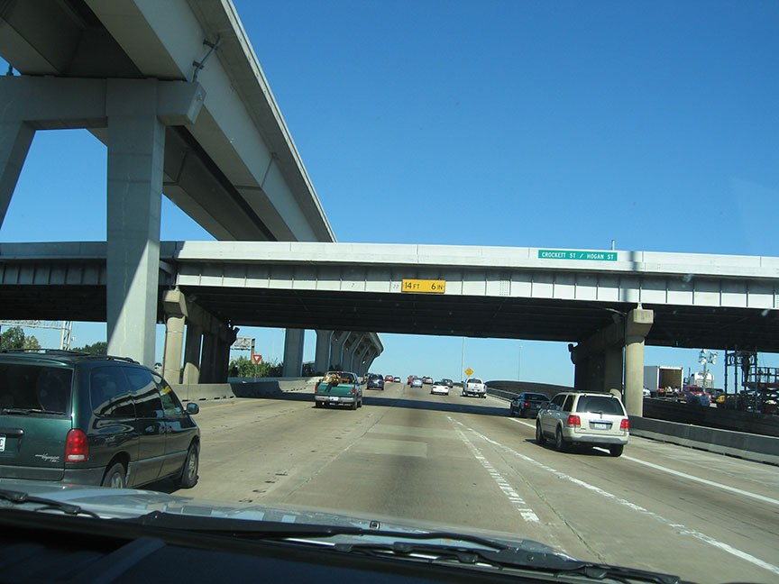 A series of highway overpasses at different intersections; traffic flows in front of the truck, bright blue skies stretch overhead