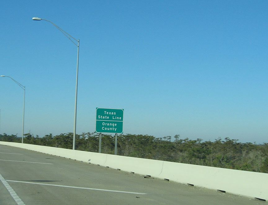 "A green road sign stands just on the other side of the barrier and reads ""Texas State Line; Orange County"""