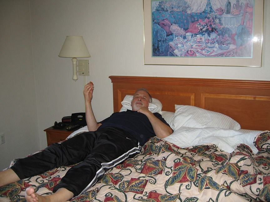 Rick Gifford lays on a hotel bed, relaxing and smiling to the camera