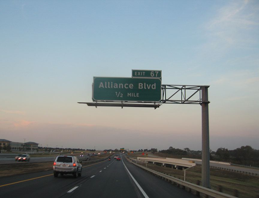 "A green road sign hangs over the roadway and reads ""Alliance Blvd""; the sky is blue with dusty pink at the horizon"