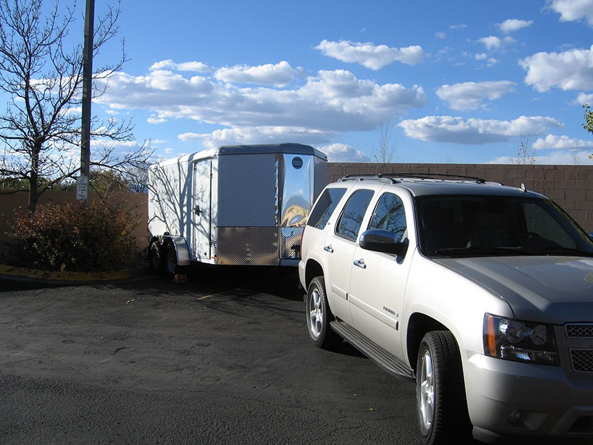 A silver Tahoe SUV sits in front of an enclosed trailer; behind it blue sky with white fluffy clouds stretches overhead