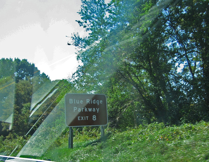 "A brown side reads ""Blue Ridge Parkway"" and stands in tall grass off the shoulder of the road"