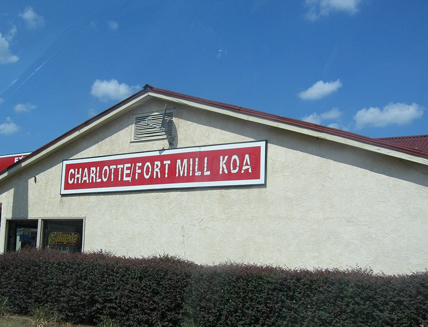 "A beige stucco building with a red sign that reads ""Charlotte/Fort Mill KOA"""