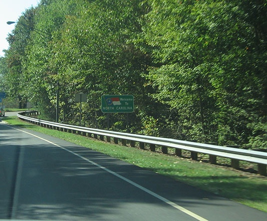 "A green sign with the flag of North Carolina reads ""Welcome to North Carolina"" and stands just beyond the barrier near a tree line"