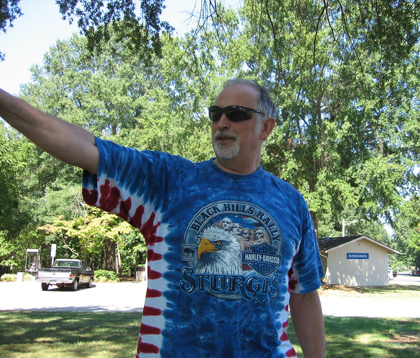 Rick looks at something off camera, following his outstretched right hand; a small white building and trees are behind him