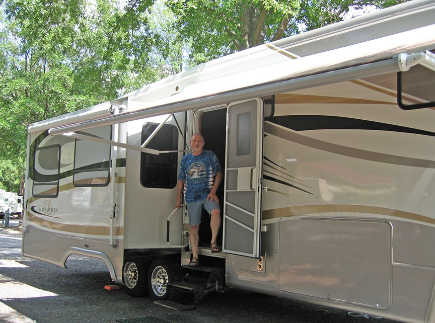 Rick stands in the door of the fifth wheel, smiling to the camera as the fifth wheel is parked and full set up.