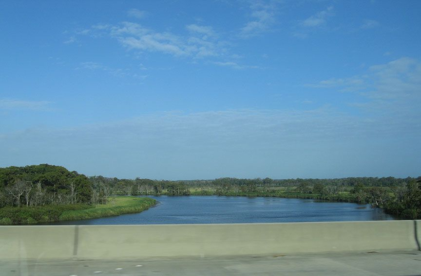 A river stretches out passed the shoulder of the highway, curving through trees; a blue sky stretches over the river