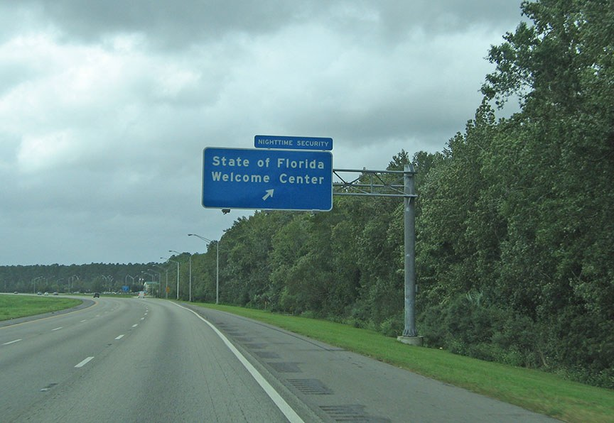 "A blue sign extends over the highway and reads ""State of Florida Welcome Center"""