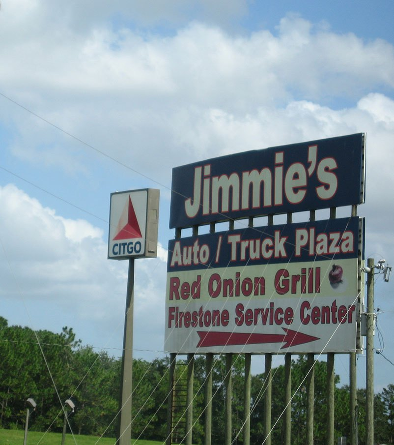 """A large sign on the side of the road reads """"Jimmi'es Auto/Truck Plaza Red Onion Grill & Firestone Service Center"""""""