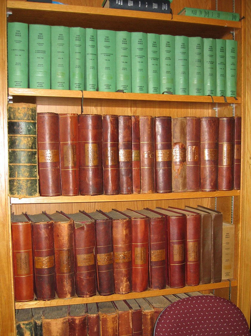 A bookshelf is laden with volumes of antique books