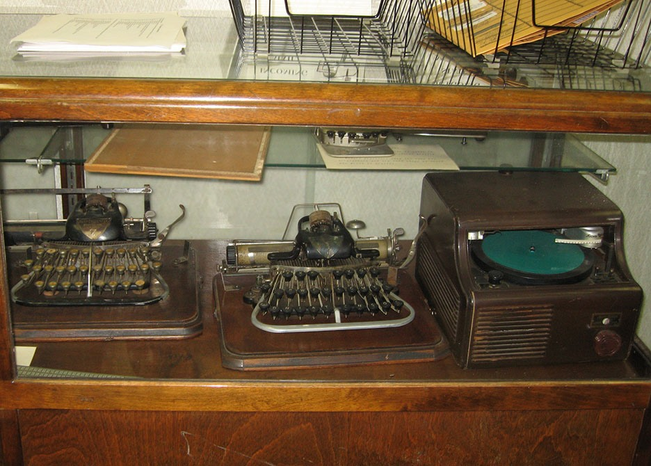 Three different antique Braille embossers sit inside a wooden and glass display case; wire baskets sit on top of the case
