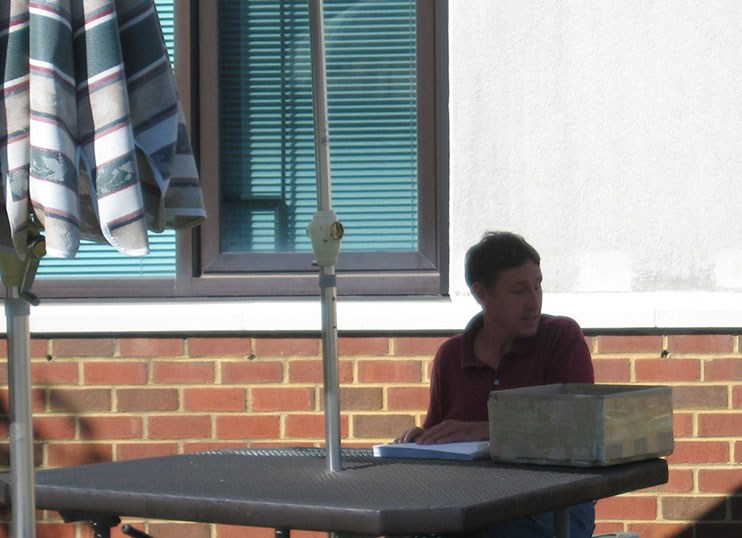 A staff member of DBVI sits at a table outside, under an umbrella, proofreading a Braille document