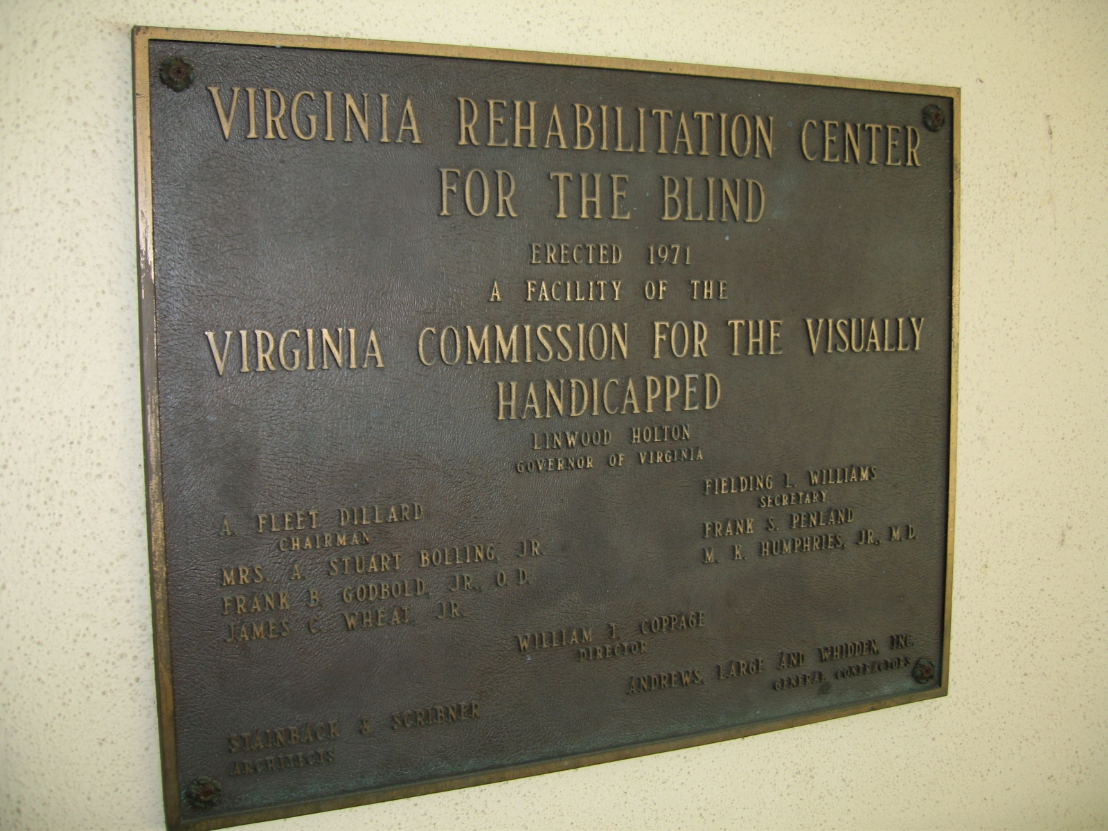 """A plaque hangs on a wall and reads """"Virginia Rehabilitation Center for the Blind"""" and """"Virginia Commission for the Visually Handicapped"""""""