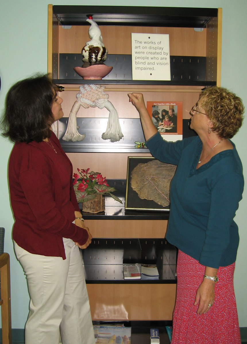 "Lisa Gifford looks on as staff member from DBVI gestures to a bookshelf filled with artwork; a sign on a shelf reads ""The works of art on display were created by people who are blind and vision impaired"""